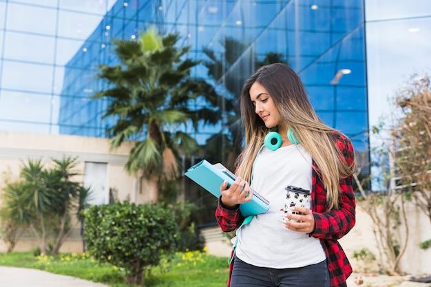 Portret van een tiener die stapel van boeken en meeneemkoffiekop bekijkt tegen de universitaire bouw