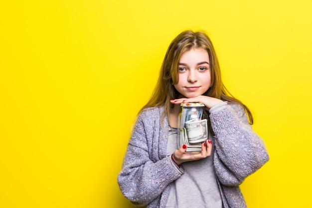 Portret van een tiener donkerbruin meisje met geïsoleerd cuppingglassgeld. pot met geld in tienerhanden