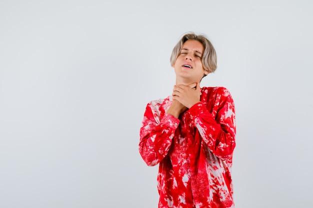 Portret van een tienerblonde man die een zelfmoordgebaar maakt in een te groot shirt en er hopeloos uitziet aan de voorkant