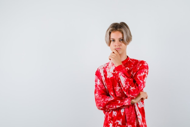 Portret van een tienerblonde man die in een denkende pose staat in een te groot hemd en een verbaasd vooraanzicht kijkt