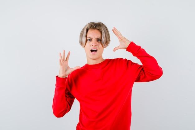 Portret van een tienerblonde man die zijn handen op een agressieve manier in een rode trui uitrekt en woedend vooraanzicht kijkt