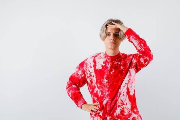 Portret van een tienerblonde man met de hand over het hoofd in een oversized shirt en een gefocust vooraanzicht