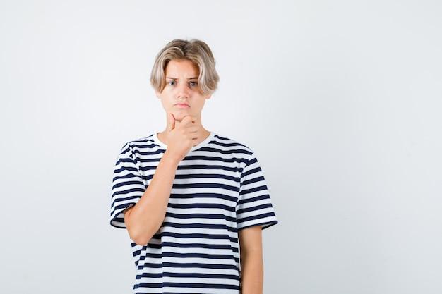 Portret van een tienerjongen die de hand op de kin in een t-shirt houdt en er geïnteresseerd vooraanzicht uitziet