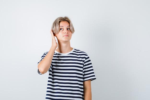 Portret van een tienerjongen die de hand op het oor houdt in een t-shirt en er charmant vooraanzicht uitziet