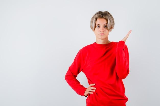 Portret van een tienerjongen die de palm in een rode trui uitspreidt en er zelfverzekerd vooraanzicht uitziet
