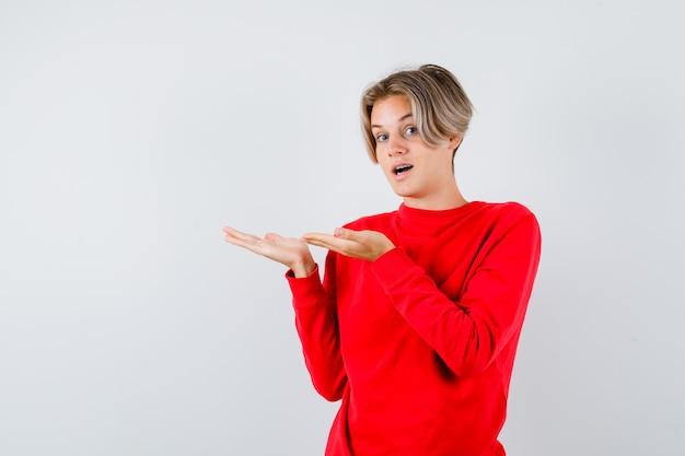 Portret van een tienerjongen die doet alsof hij iets laat zien, zijn mond opent in een rode trui en een verbaasd vooraanzicht kijkt