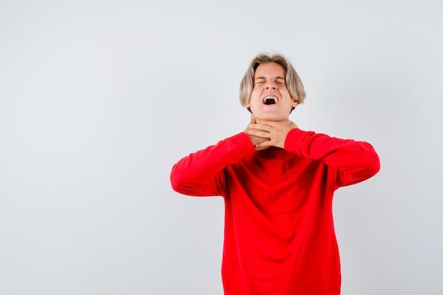Portret van een tienerjongen die lijdt aan keelpijn in een rode trui en er ziek uitziet vooraanzicht