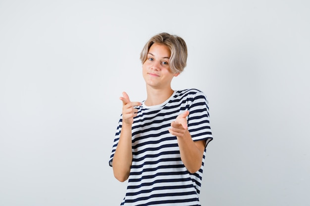 Portret van een tienerjongen die naar voren wijst in een t-shirt en er vrolijk vooraanzicht uitziet