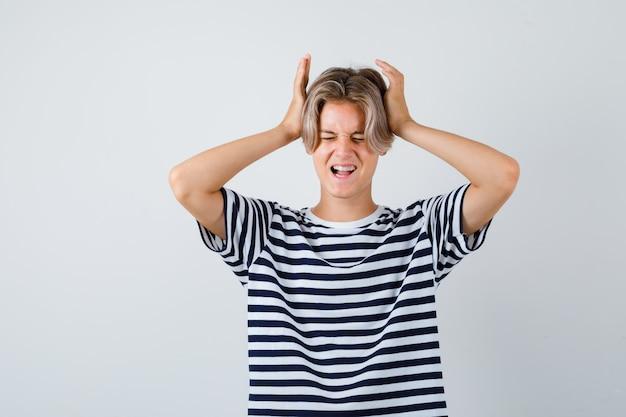 Portret van een tienerjongen met handen op het hoofd, mond openend in t-shirt en woedend vooraanzicht kijkend