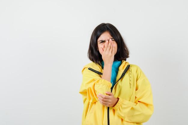 Portret van een tienermeisje dat de hand op de mond houdt in een gele jas en er bedroefd vooraanzicht uitziet