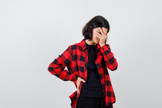 Portret van een tienermeisje dat de hand op het gezicht houdt, de hand op de taille houdt in een casual shirt en er uitgeput uitziet