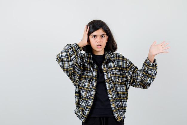 Portret van een tienermeisje dat de hand op het hoofd houdt, een welkomstgebaar toont in een casual shirt en een geschokt vooraanzicht toont