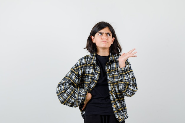 Portret van een tienermeisje dat de handpalm opzij spreidt, de hand op de taille houdt in een casual shirt en een besluiteloos vooraanzicht kijkt