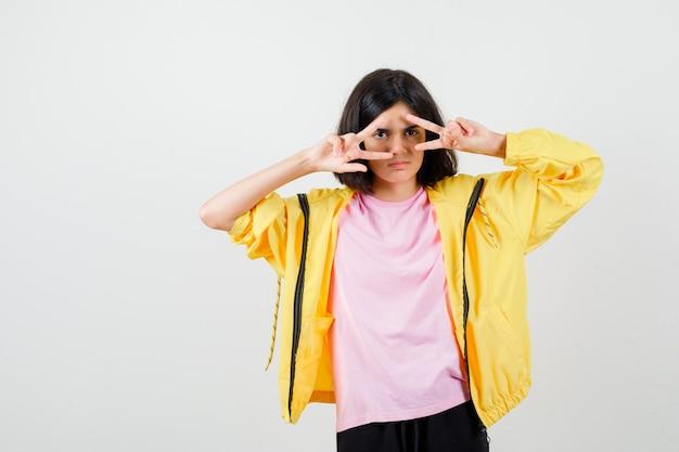 Portret van een tienermeisje dat door de vingers in een t-shirt, een jas kijkt en een ongezellig vooraanzicht ziet