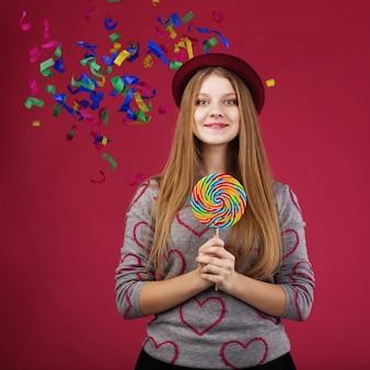 Portret van een tienermeisje dat een kleurrijke lolly houdt