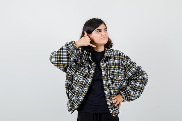 Portret van een tienermeisje dat een telefoongebaar toont, de hand op de taille houdt in een casual shirt en er een gelukzalig vooraanzicht uitziet