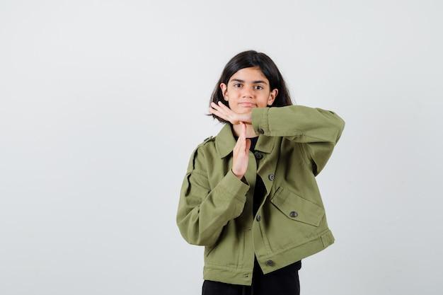 Portret van een tienermeisje dat een tijdsonderbrekingsgebaar toont in een legergroen jasje en er ontmoedigd vooraanzicht uitziet