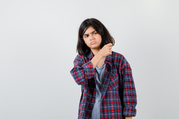 Portret van een tienermeisje dat gebaren maakt terwijl ze wegkijkt in vrijetijdskleding en er somber uit ziet