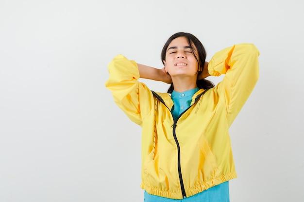 Portret van een tienermeisje dat haar achter de nek stopt, de ogen dicht houdt in een gele jas en er ontspannen vooraanzicht uitziet
