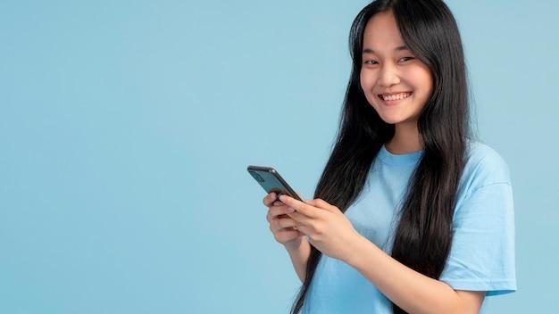 Portret van een tienermeisje dat haar telefoon controleert met kopieerruimte
