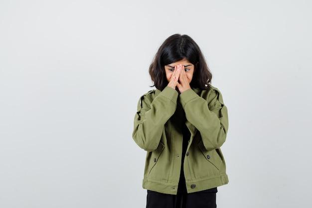 Portret van een tienermeisje dat handen op het gezicht houdt in een legergroen jasje en angstig vooraanzicht kijkt