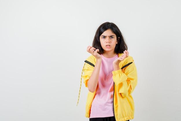 Portret van een tienermeisje dat handen vasthoudt in de buurt van gezicht in t-shirt, jas en boos vooraanzicht kijkt