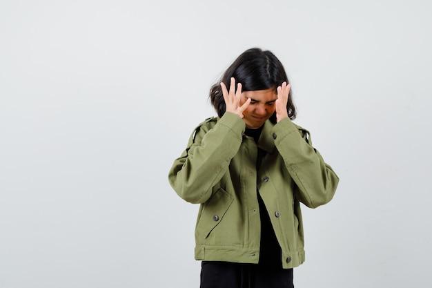 Portret van een tienermeisje dat handen vasthoudt in de buurt van het hoofd in een legergroen jasje en er geïrriteerd vooraanzicht uitziet