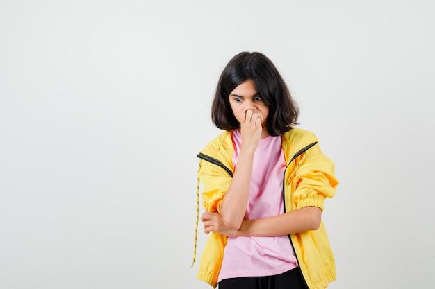 Portret van een tienermeisje dat in een denkende pose staat in een t-shirt, een jas en een verbaasd vooraanzicht kijkt