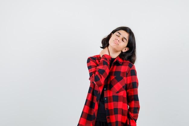 Portret van een tienermeisje dat lijdt aan nekpijn in een casual shirt en er onwel uitziet aan de voorkant