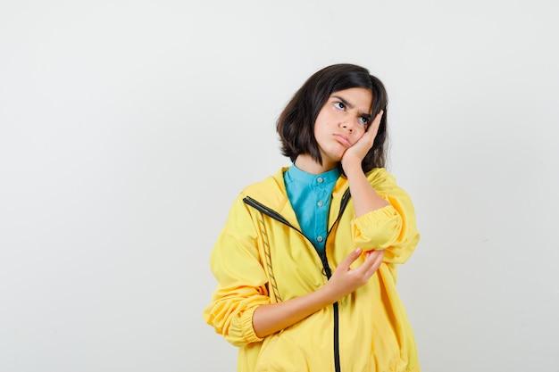 Portret van een tienermeisje dat met de wang op de handpalm leunt, wegkijkt in een gele jas en er somber uitziet
