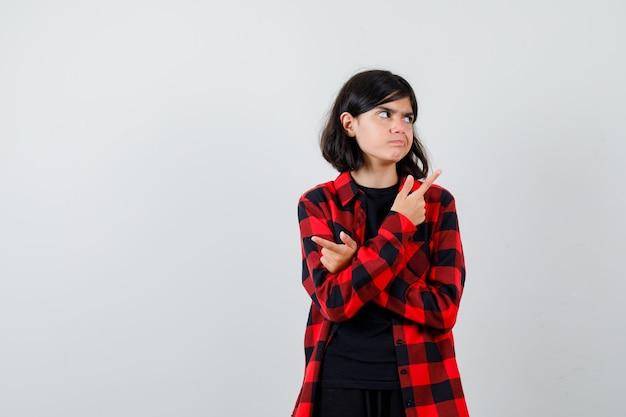 Portret van een tienermeisje dat met gekruiste handen naar tegenovergestelde richtingen wijst, opzij kijkt in een casual shirt en aarzelend vooraanzicht kijkt