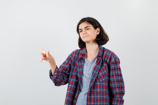 Portret van een tienermeisje dat naar de linkerbovenhoek wijst, wegkijkt in vrijetijdskleding en er somber uitziet