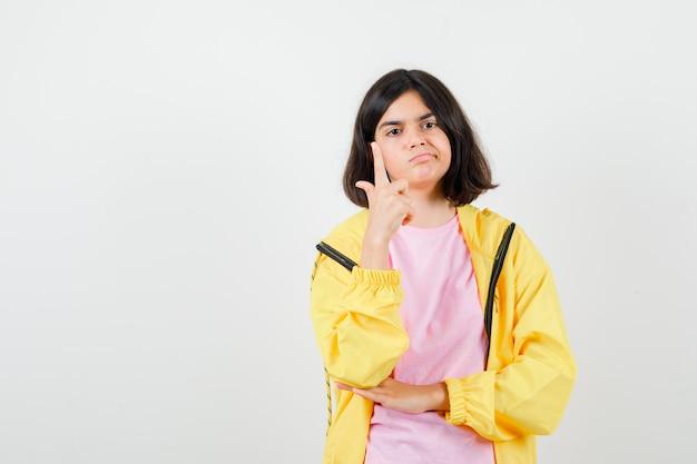 Portret van een tienermeisje dat omhoog wijst in een t-shirt, jas en zelfverzekerd vooraanzicht