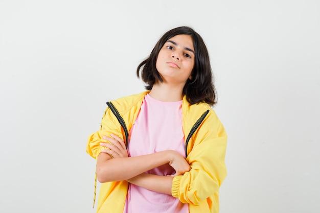 Portret van een tienermeisje hand in hand gekruist in t-shirt, jas en zelfverzekerd vooraanzicht