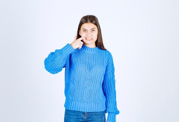 Portret van een tienermeisje in een blauwe trui die haar tanden op de witte muur aanraakt.