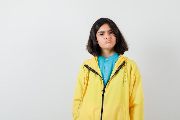 Portret van een tienermeisje in een gele jas en een somber vooraanzicht