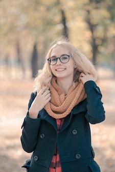 Portret van een tienermeisje in grote zwarte glazen in een herfstpark
