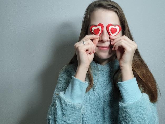 Portret van een tienermeisje met een hart in haar hand, gefeliciteerd met valentijnsdag