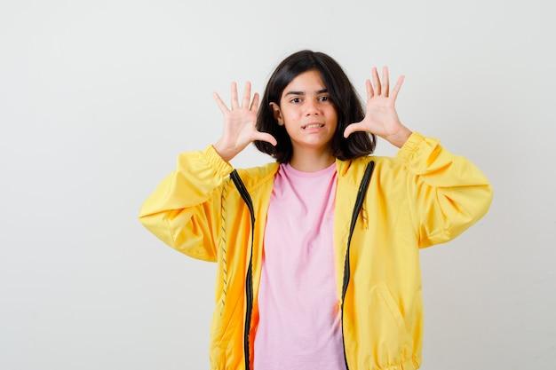 Portret van een tienermeisje met een overgavegebaar in een t-shirt, een geel jasje en een verbijsterd vooraanzicht