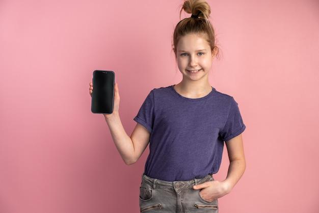 Portret van een tienermeisje met een slimme telefoon met een zwart leeg scherm op een roze muur