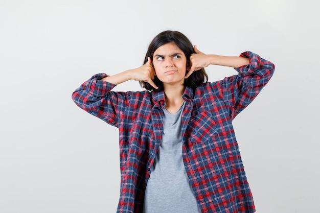 Portret van een tienermeisje met een telefoongebaar, wegkijkend in vrijetijdskleding en een gefocust vooraanzicht