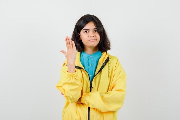 Portret van een tienermeisje met nagels in shirt, gele jas en nieuwsgierig vooraanzicht