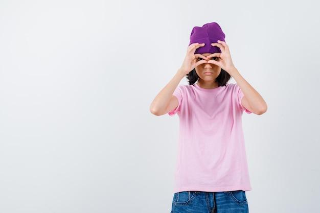 Portret van een tienervrouw die een brilgebaar toont in een t-shirt en een muts die er nieuwsgierig uitziet
