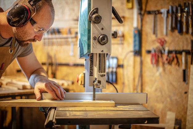 Portret van een timmerman binnen zijn timmerwerkworkshop die een lintzaag gebruikt.