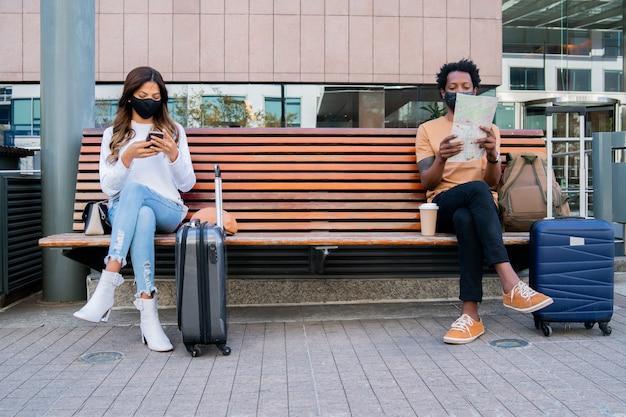 Portret van een toeristenmensen die buiten luchthaven of treinstation wachten terwijl ze op een bank zitten en afstand houden. toerisme concept. nieuw normaal levensstijlconcept.