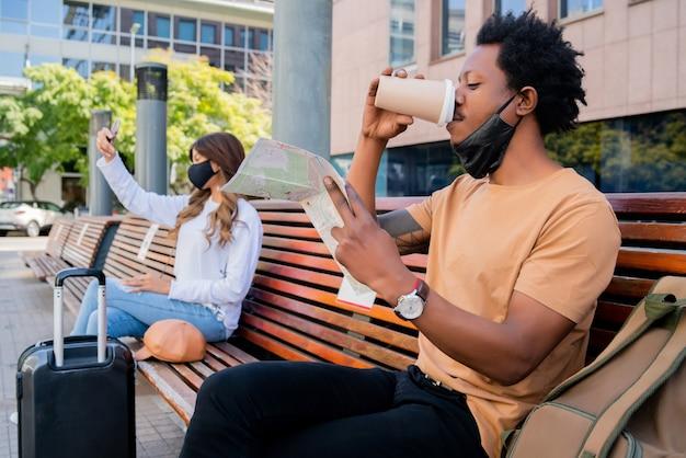 Portret van een toeristenmensen die buiten luchthaven of treinstation wachten terwijl ze op een bank zitten en afstand houden. toerisme concept