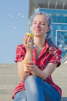 Portret van een toevallig leuk en jong meisje met blauwe haar blazende zeepbels in de stad op een hete zonsondergang van de de zomer zonnige dag