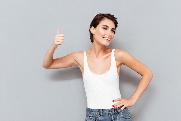 Portret van een toevallige jonge vrouw die duimen toont die omhoog op de grijze achtergrond worden geïsoleerd