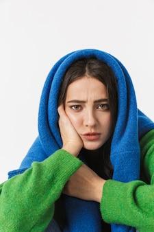 Portret van een toevallige jonge vrouw die onsized sweaterzitting op wit draagt
