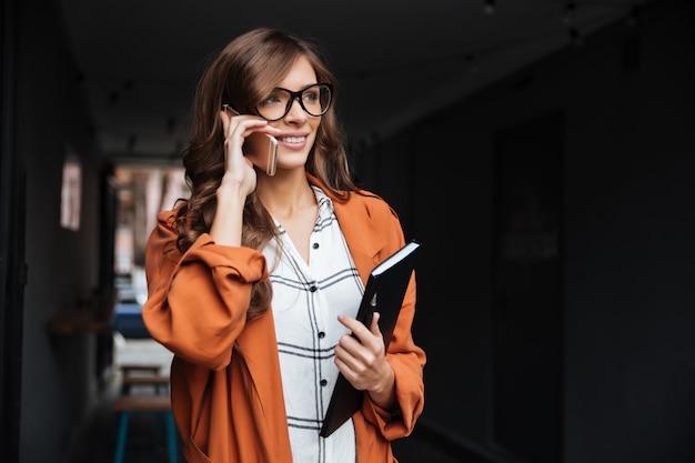 Portret van een toevallige vrouw die op mobiele telefoon spreekt